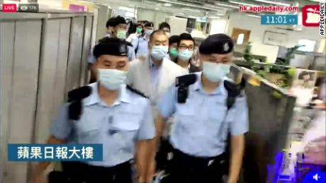 Jimmy Lai is escorted through the Apple Daily newsroom after being arrested under Hong Kong's national security law in August 2020.