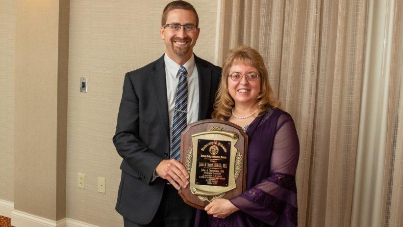 KYCOM Dean Dr. Joe Kingery presents Dr. Julia H. Smith with the John A. Strosnider Memorial Lecturer award.